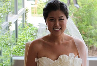An actual patient of Dr. Kazerooni's in her wedding dress smiling after receiving teeth whitening in McLean, VA